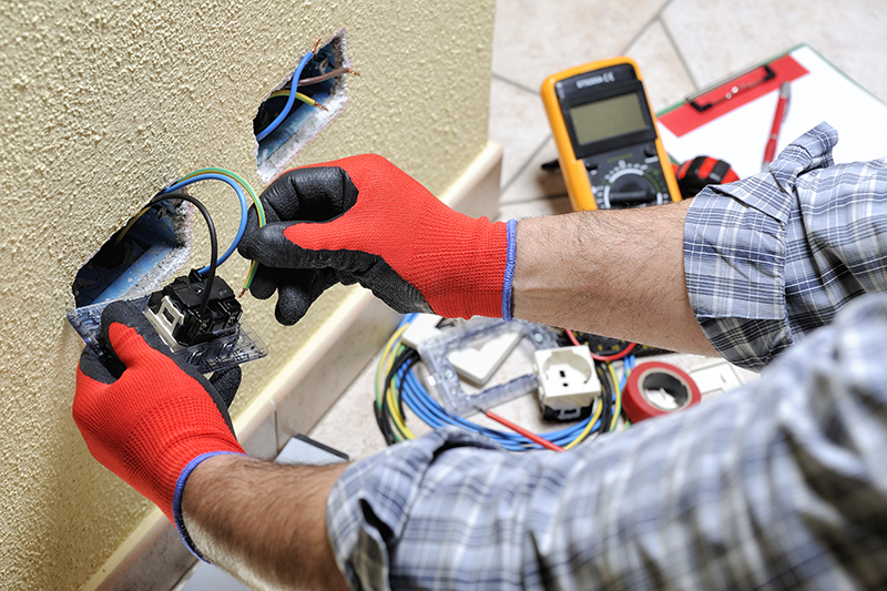 Electrician technician at work doing a residential electrical installation, which is double-checked during home inspection services